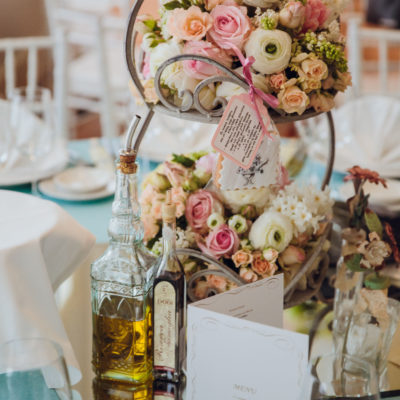 Delicate rose bouquets stand on the tired dish on a dinner table